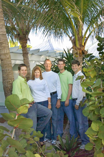 casual outdoor family portrait at their beach home by palm tree